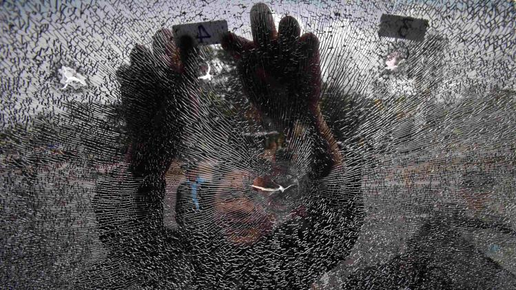 Police officer inspects the damaged windshield of a police bus after clashes between police and rubber farmers in Bangsaphan