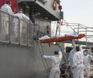 A body is being lowered down from a Maltese Navy ship …