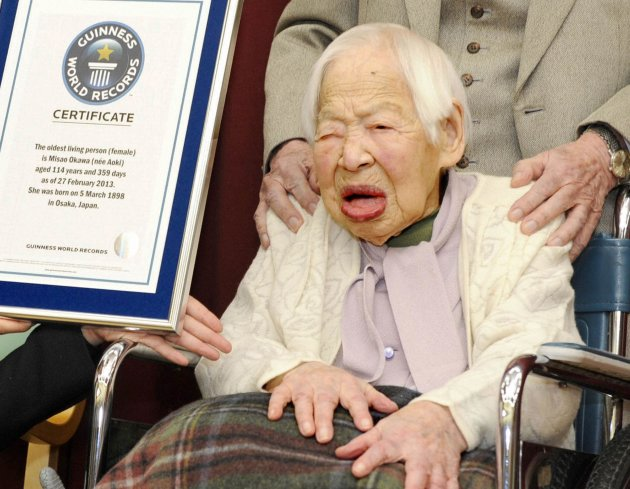 Misao Okawa receives a certification from an official of Guinness World Records in Osaka, Japan