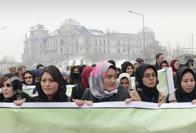 Afghan women carry a banner during a march calling for end of violence against women, in Kabul, with the Darul Aman palace seen in the background, Afghanistan, Thursday, Feb. 14, 2013. Dozens of Afgha