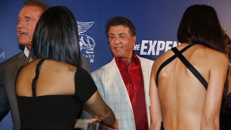 """U.S. actors, Arnold Schwarzenegger, left, and Sylvester Stallone shake hands with guests on the red carpet for the Macau premiere of their movie """"The Expendables 3"""" in Macau, China, Friday, Aug. 22, 2014. (AP Photo/Kin Cheung)"""