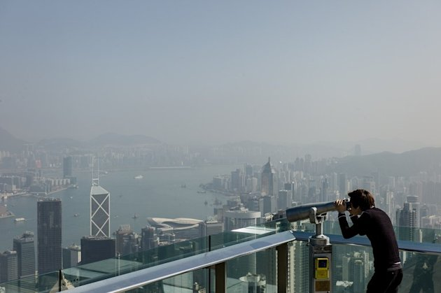 A tourist uses binoculars to view the city&#39;s skyline over a haze of pollution on a clear day in Hong Kong on February 1, 2013. A mainland Chinese mother who asked her son to relieve himself in a bottle in a crowded Hong Kong restaurant has sparked an outpouring of online anger in the latest bitter exchange over etiquette