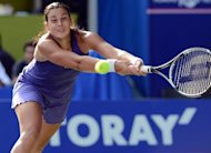 Marion Bartoli of France returns the ball against Kumiko Date-Krumm of Japan during the women's singles first round match at the Pan Pacific Open tennis in Tokyo. Bartoli defeated Date-Krumm 6-1, 6-4 to reach the second round of the Pan Pacific Open tennis tournament in Japan