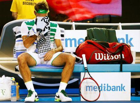 Switzerland's Federer wipes his face with a towel during his semi-final match against Serbia's Djokovic at the Australian Open tennis tournament at Melbourne Park