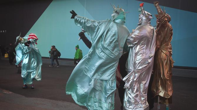 One person who dresses up as the Statue of Liberty and poses for tips, takes photos of others similarly dressed up, in Times Square, New York