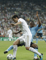 Real Madrid's Kaka from Brazil, left, duels for the ball against Ajax Eyong Enoh from Cameroon during their group D Champions League soccer match at the Santiago Bernabeu stadium, in Madrid, Tuesday, Sept. 27, 2011. (AP Photo/Daniel Ochoa de Olza)