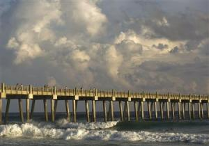 People watch surfers ride waves generated by Tropical Storm Karen atop the Pensacola Beach Pier at Pensacola Beach, Florida