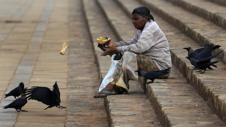 A woman feeds crows with pieces of bread from her breakfast at Galle Face Green in Colombo