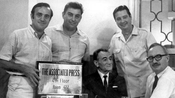 FILE - In this circa 1968-69 file photo, AP Saigon staffers, correspondent Peter Arnett, left; photo chief Horst Faas, second left; Chief of Bureau George McArthur, second right; and Edwin Q. White, right, pose for a photo with Jean Ottavi, owner of the Royal Hotel in Saigon. McArthur, a former AP foreign correspondent who reported all over the world and spent years in Saigon covering the Vietnam war, has died. He was 88. His wife, Eva Kim McArthur said he died Friday night, April 12, 2013 in a hospice in Fairfax County, Va., of complications from a stroke. (AP Photo)