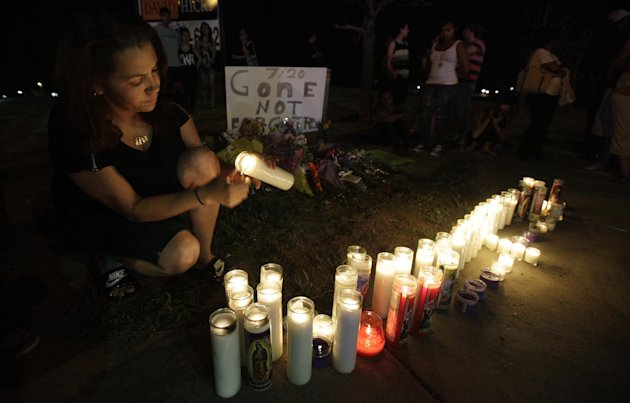 Esmeralda Carbajal lights candles at a growing memorial across the street from the Century 16 movie theater, late Friday, July 20, 2012, in Aurora, Colo., nearly 24 hours after a gunman killed at least 12 people and wounded dozens of others watching the latest Batman film in one of the deadliest mass shootings in recent U.S. history. (AP Photo/Ted S. Warren)