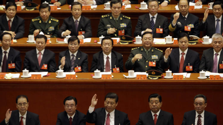 Chinese Vice President Xi Jinping, center in front row, keeps his hand up during a show of approval for a work report during the closing ceremony for the 18th Communist Party Congress at the Great Hall of the People in Beijing Wednesday Nov. 14, 2012. (AP Photo/Ng Han Guan)