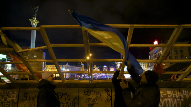 Teenagers wave a national flag attached to a barricade protecting the central Independence square from possible police attack during a rally in Kiev, Ukraine, on Monday, Dec. 2, 2013. Thousands of protesters besieged government buildings in Ukraine's capital on Monday to demand the ouster of the prime minister and his Cabinet, as anger at the president's decision to ditch a deal for closer ties with the European Union gripped other parts of the country and threatened his rule. (AP Photo/Ivan Sekretarev)