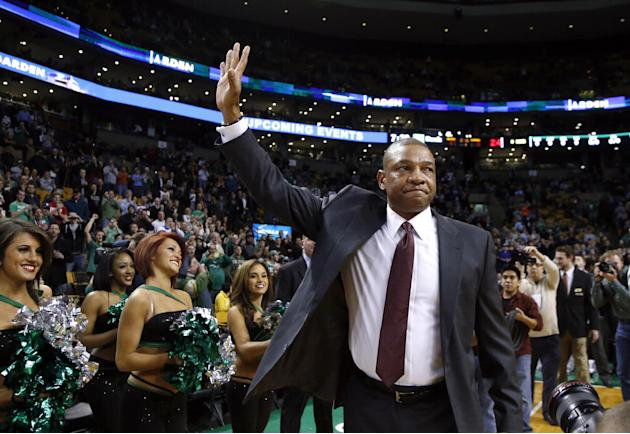 Doc Rivers, former head coach of the Boston Celtics and current head coach of the Los Angeles Clippers, waves to cheering fans as he enters the TD Garden floor for his first time back, before an NBA b