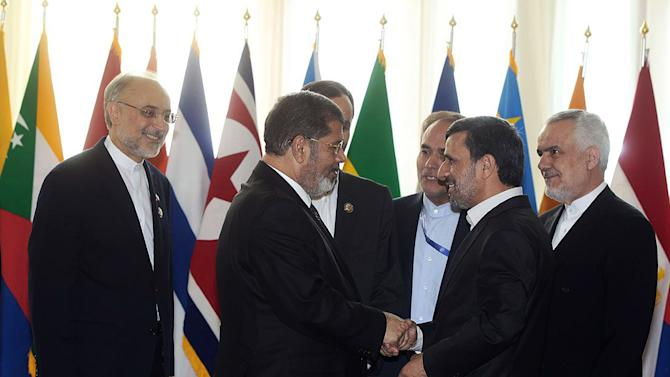 """In this photo released by the official website of the Iranian presidency office, Iranian President Mahmoud Ahmadinejad, second right, welcomes Egyptian President Mohammed Morsi for the opening session of the Nonaligned Movement, NAM, summit, in Tehran, Iran, Thursday, Aug. 30, 2012. Morsi described the Syrian regime as """"oppressive"""" and called for it to transfer power to a democratic system during a visit to Syria's key regional ally Iran on Thursday. Iranian Vice-President Mohammad Reza Rahimi stands at right, and Foreign Minister Ali Akbar Salehi, left. (AP Photo/Presidency Office)"""