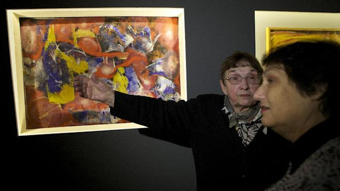 In this photo taken on Thursday, Dec. 5, 2012, artist Inna Shmelyova, second right, speaks to a visitor at the opening of an exhibition at Moscow's Manezh hall , Russia. Shmelyova was one of the artists whose works were banned by Soviet leader Nikita Khruschev at a similar 1962 exhibition at the Manezh hall. Fifty years later, some of the banned canvases are on display again at the same Manezh hall _ at a time when critics compare Khruschev's ban to recent charges against the Pussy Riot band and artists whose paintings have angered the Kremlin and Russia's dominant Orthodox Church.(AP Photo/Alexander Zemlianichenko)