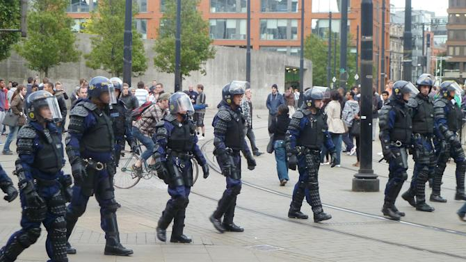 Riot police patrol Manchester city centre after trouble  on Market street  in Manchester city centre, England,  Tuesday Aug. 9, 2011.  Britain began flooding London's streets with 16,000 police officers Tuesday, nearly tripling their presence as the nation feared its worst rioting in a generation would stretch into a fourth night. The violence has turned buildings into burnt out carcasses, triggered massive looting and spread to other U.K. cities.   (AP Photo /  Dave Thompson / PA)  UNITED KINGDOM OUT