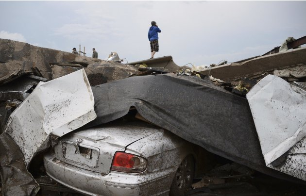 A damaged car is seen as a resident stands on top of wreckage after a tornado struck Moore, Oklahoma