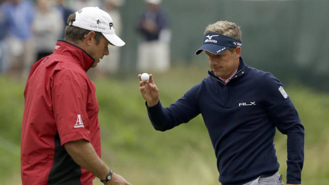 Luke Donald, right, of England, reacts after a putt on the 17th hole as Lee Westwood, of England, walks the green during the first round of the U.S. Open golf tournament at Merion Golf Club, Friday, June 14, 2013, in Ardmore, Pa. (AP Photo/Gene J. Puskar)