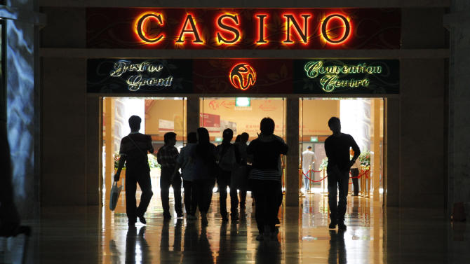 In this photo taken on Sept. 4, 2012, people make their way to the casino at Resorts World Sentosa in Singapore. In the Philippines, a $4 billion casino project will soon rise from reclaimed land on Manila Bay. In South Korea, foreign investors will break ground next year on a clutch of casino resorts offshore. The projects are part of a casino building boom rolling across Asia, where governments are trying to develop their tourism markets to capture increasingly affluent Asians with a penchant for gambling. (AP Photo/Wong Maye-E)
