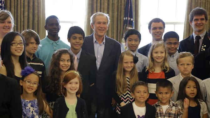 Former President George W. Bush, center, poses with 43 students from Dallas-Fort Worth area schools who were the first 43 official guest to tour the Bush Presidential Library on its' opening day Wednesday, May 1, 2013, in Dallas. Bush surprised the group in the replica of the oval office. (AP Photo/Tony Gutierrez)