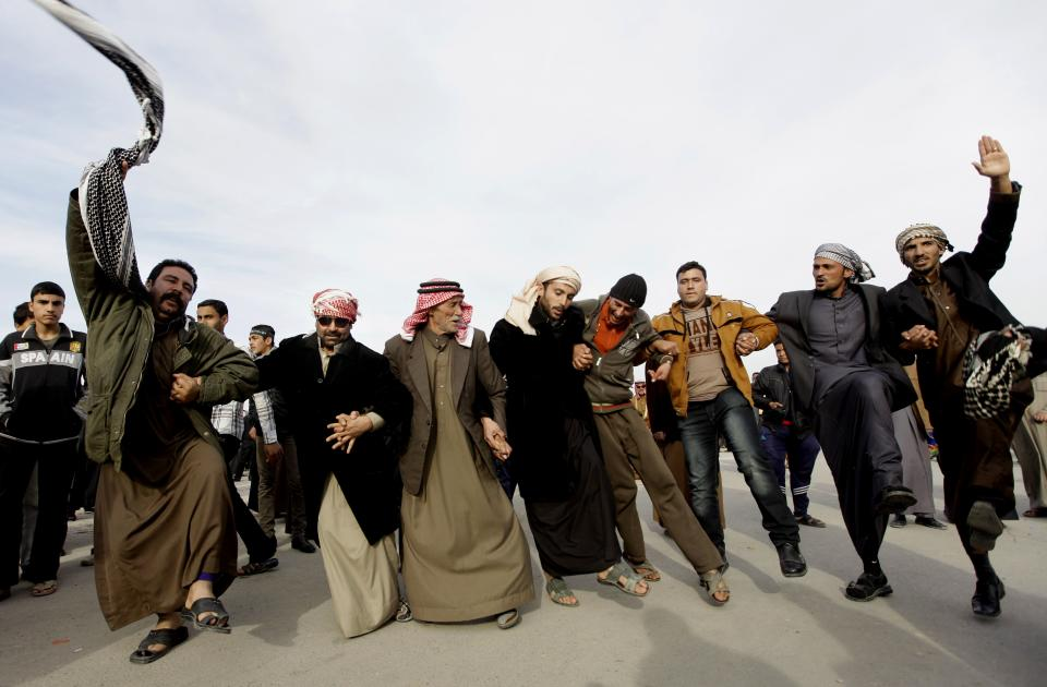Protesters dance during a demonstration in Ramadi, 70 miles (115 kilometers) west of Baghdad, Iraq, Thursday, Jan. 24, 2013. Thousands of Iraqi Sunnis massed along a major western highway in a demonstration, intensifying pressure on the Shiite-led government. (AP Photo/ Khalid Mohammed)