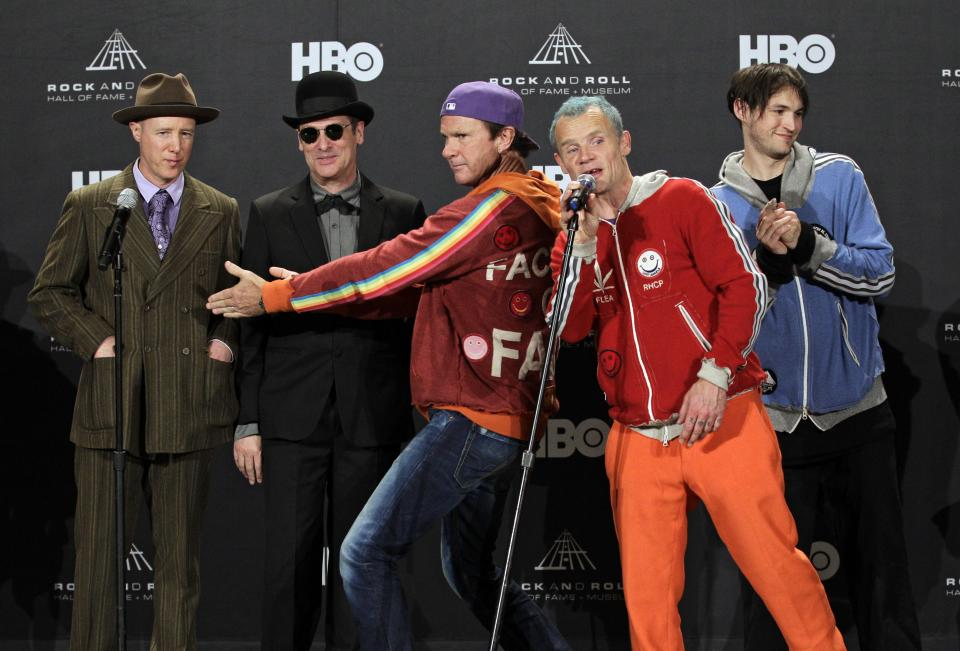 "Red Hot Chili Peppers drummer Chad Smith, center, introduces former members Jack Irons, left, and Cliff Martinez with Mike ""Flea"" Balazary, second from right, and Josh Klinghoffer before the group was inducted into the  Rock and Roll Hall of Fame Friday, April 13, 2012, in Cleveland. (AP Photo/Amy Sancetta)"