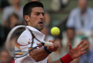 Serbia's Novak Djokovic slams a ball to Switzerland's Roger Federer during their semi final match for the French Open tennis tournament at the Roland Garros stadium in Paris, Friday June 3, 2011. Federer won 7-6, 6-3, 3-6, 7-6.