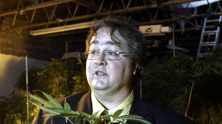 In this March 28, 2011 photo, Paul Stanford holds a marijuana plant in his growing facility in Portland, Ore. Stanford, one of the nation's leading marijuana legalization advocates, doesn't only want Oregonians to have the right to smoke pot. He wants it written into the state constitution. Stanford's proposed constitutional amendment is one of several pot questions that may go to Oregon voters in November. Others are offering competing measures for how the state would regulate and tax the drug. (AP Photo/Rick Bowmer)