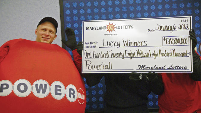 FILE - In this Jan. 6, 2012 file photo provided by the Maryland State Lottery Agency, a man dressed as a Powerball stands by a couple who did not want to be identified as they hold a large prop check showing their winnings at the lottery's headquarters in Baltimore. In cases in which simple dumb luck suddenly changes someone's fortunes, observers say such clinging to anonymity despite the glaring spotlight is just plain smart. Illinois lottery officials are still waiting for the winner who bought a ticket worth $218 million in the small town of Red Bud, Ill., to come forward. It was part of a three-way share in the $656 million Mega Millions jackpot drawn on March 30.  (AP Photo/Maryland State Lottery Agency, File)