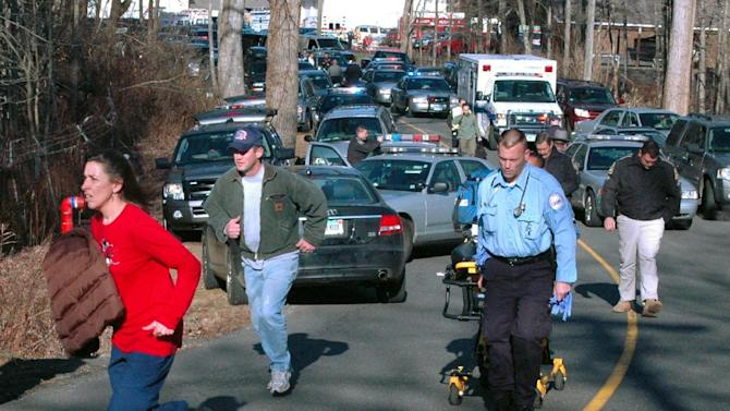 FILE - In this Dec. 14, 2012 file photo provided by the Newtown Bee, paramedics and others rush toward Sandy Hook Elementary School in Newtown, Conn., shortly after Adam Lanza opened fire, killing 26 people, including 20 children. While the people of Newtown do their best to cope with loss and preserve the memories of their loved ones, another class of residents is also finding it difficult to move on: the emergency responders who saw firsthand the terrible aftermath of last week's school shooting. (AP Photo/Newtown Bee, Shannon Hicks, File) MANDATORY CREDIT: NEWTOWN BEE, SHANNON HICKS