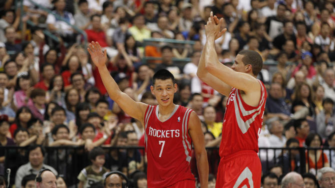Houston Rockets Jeremy Lin (7) cheers with Francisco Garcia after scoring against the Indiana Pacers during a preseason game in Taipei, Taiwan, Sunday, Oct. 13, 2013. The Rockets beat the Pacers 107-98. (AP Photo/Wally Santana)