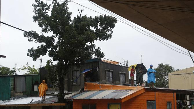 People wait to be rescued as they stand on the roof of their homes as tropical storm Fung-Wong battered the Philippine capital Manila