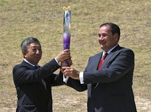 Ser Miang Ng (left) holds the Olympic flame with Spyros Capralos of Greece at a ceremony in Olympia in July 2010. (AFP File Photo)
