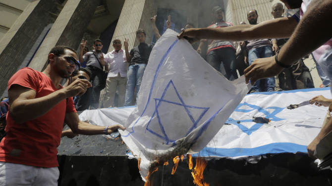 FILE - In this file photo taken Sunday, July 13, 2014, Egyptian journalists burn a representative of the Israel flag to protest against the Israeli operations in Gaza, while holding a demonstration in front of the Syndicate of Journalists building in Cairo, Egypt. In the Gaza war, the Palestinian Hamas is demanding the opening of Egypt's Sinai border crossing into blockaded Gaza, but Egypt is so far staunchly refusing _ a reflection of its sharp rivalry with Hamas, which it accuses of fueling militancy on its soil. (AP Photo/Amr Nabil, File)