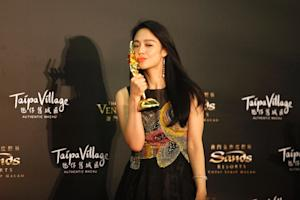Zhou Yun kisses the trophy after winning the best supporting…