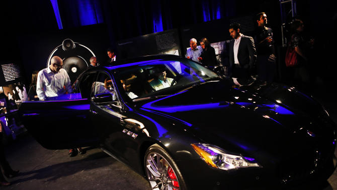IMAGE DISTRIBUTED FOR BOWERS & WILKINS - Guests interact with the Maserati Quattroporte during the Bowers & Wilkins and Maserati Seven Notes World Tour event at Industria Superstudio, Thursday, June 13, 2013, in New York. (John Minchillo/AP Images for Bowers & Wilkins)
