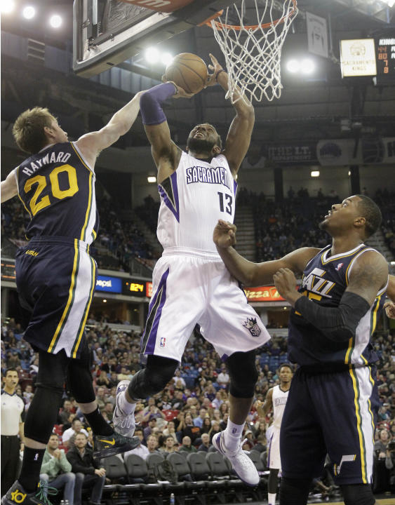 Sacramento Kings forward Derrick Williams, center, goes to the basket between Utah Jazz' Gordon Hayward, left, and  Derrick Favors during the third quarter of an NBA basketball game in Sacramento,