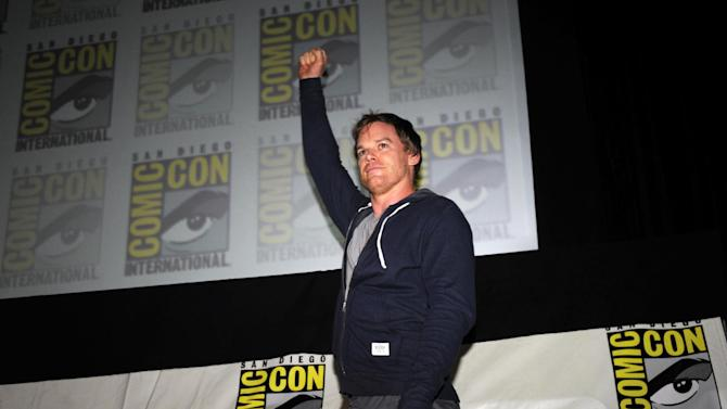 """Actor Michael C. Hall pumps his fist as he walks onto stage start of the """"Dexter"""" panel on Day 2 of the 2013 Comic-Con International Convention on Thursday, July 18, 2013 in San Diego. (Photo by Denis Poroy/Invision/AP)"""