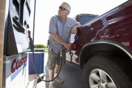 In this Aug. 9, 2011 photo, Gary Hartwig of Gretna, Neb., fuels his car at a Costco gas station in Omaha, Neb. Consumers spent more on autos, furniture and gasoline in July, pushing up retail sales by the largest amount in four months. The gain could signal that Americans are a little more confident and help dispell fears that the country is in danger of toppling into another recession. (AP Photo/Nati Harnik)