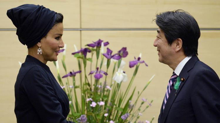 Qatar's Sheikha Mozah, Consort of the Father Emir of Qatar and Chairperson of the Qatar Foundation, and Japan's PM Abe shake hands before their meeting at the latter's official residence in Tokyo