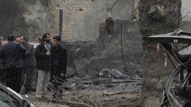 A victim is seen at the scene of a suicide car bomb attack in Kabul, Afghanistan, Wednesday, Jan. 16, 2013. Six militants — one driving a car packed with explosives — attacked the gate of the Afghan intelligence service in the capital Kabul on Wednesday, setting off a blast that could be heard throughout downtown and which sent a plume of dark smoke rising into the sky. (AP Photo/Ahmad Jamshid)