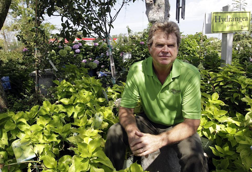 In this Aug. 3, 2012, photo Jeff Gatewood, owner of Allisonville Nursery, poses in his nursery in Fishers, Ind. The nursery held a heat stroke sale in late July, offering customers a chance to buy plants and pick them up later, once cooler temperatures arrive and local watering bans are lifted. (AP Photo/Michael Conroy)