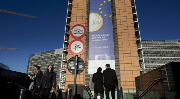 People walk in front of a giant banner for the euro currency outside of an EU summit in Brussels on Thursday, Nov. 22, 2012. Leaders from around Europe are arriving in Brussels Thursday for what promi