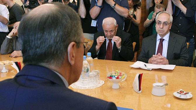 Russian Foreign Minister Sergey Lavrov, back to camera, meets with a delegation headed by a leader of the Syrian National Council (SNC), Abdulbaset Sieda, right, in Moscow, Russia, Wednesday, July 11, 2012. (AP Photo/Misha Japaridze)