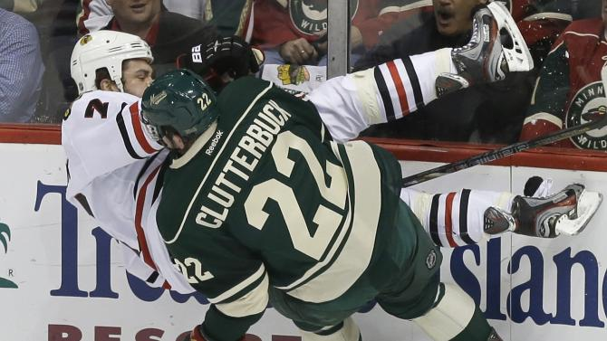 Chicago Blackhawks' Brent Seabrook gets checked into the wall by Minnesota Wild's Cal Clutterbuck in the first period of Game 4 of an NHL hockey Stanley Cup playoff series, Tuesday, May 7, 2013 in St. Paul, Minn. (AP Photo/Jim Mone)