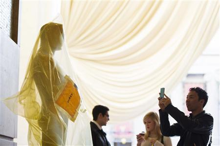 A tourist takes a photograph of an Oscar statue on the red carpet during preparations for the 85th Academy Awards in Hollywood, California, February 21, 2013. REUTERS/Lucas Jackson