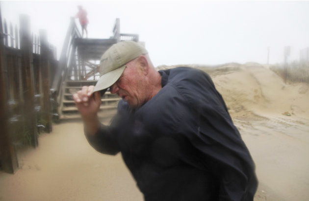 Summer resident Jody Bowers braces himself from a blast of sand and driving rain as he makes his way to the beach in Kill Devil Hills, Outer Banks, N.C., Saturday, Aug. 27, 2011 as Hurricane Irene rea