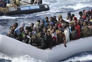 Migrants sit in a boat during a rescue operation by Italian navy off the coast of the south of the Italian island of Sicily in this November 28, 2013 picture provided by the Italian Marina Militare. REUTERS/Marina Militare/Handout via Reuters