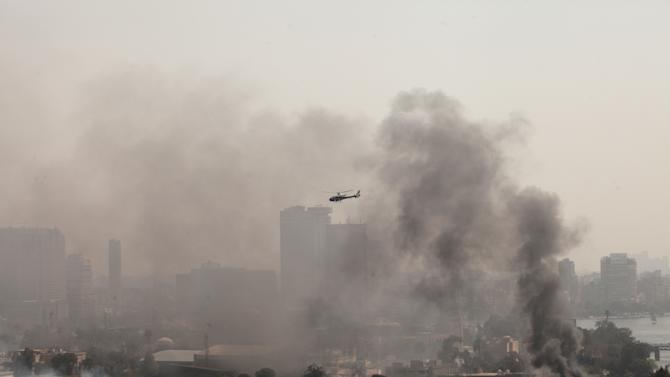 Smoke rises from the Police Officers Club, left, and the Egyptian Soccer Federation, right, as a police helicopter surveys the scene after protesters set fire following a court verdict in Saturday, March 9, 2013. Fans of Cairo's Al-Ahly club have stormed Egypt's soccer federation headquarters, set it ablaze after a court acquitted seven of nine police official on trial for their alleged part in deadly stadium melee. A fire also broke out Saturday in a nearby police club, but it was not immediately known whether Al-Ahly fans started the blaze there too. (AP Photo/Maya Alleruzzo)