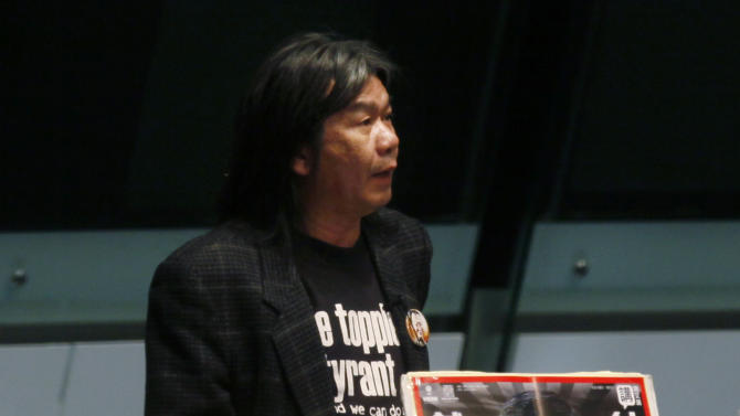 """Leung Kwok-hung, also known as Long Hair, a member of the Legislative Council displays a picture of Hong Kong's leader, Leung Chun-ying and a placard reading """" Don't want a liar Leung Chun-ying,""""  as he addresses the legislature to impeach the Beijing -backed leader, at the legislative chamber in Hong Kong Wednesday, Jan. 9, 2013. Lawmakers were making a symbolic attempt Wednesday to impeach Leung Chun-ying, the latest sign of the widening gulf between the semiautonomous southern Chinese city and its political masters in Beijing. (AP Photo/Kin Cheung)"""